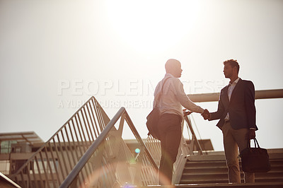 Buy stock photo Cropped shot of handsome businessmen shaking hands on top of a staircase outside
