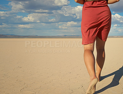 Buy stock photo Cropped shot of a young woman walking barefoot in the desert