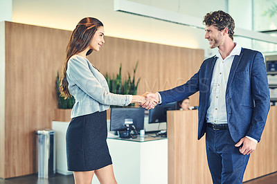 Buy stock photo Cropped shot of a businessman and businesswoman greeting by handshake in a lobby