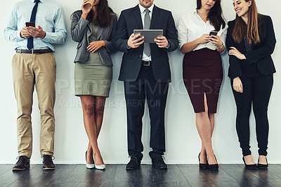 Buy stock photo Studio shot of a group of businesspeople using wireless technology while standing in line