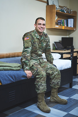 Buy stock photo Shot of a young soldier sitting on his bed in the dorms of a military academy