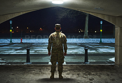 Buy stock photo Rearview shot of a young soldier standing outside on a cold night at a military academy