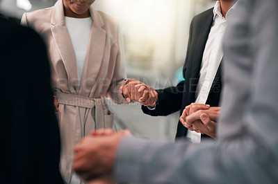 Buy stock photo Cropped shot of a group of unrecognizable businesspeople holding hands in support while standing in their office