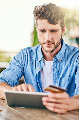 Buy stock photo Shot of a cheerful young man doing online shopping on his digital tablet and holding his credit card while being seated at a table