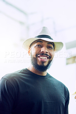 Buy stock photo Low angle portrait of a handsome young man wearing a hat
