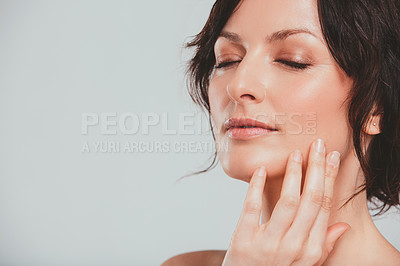 Buy stock photo Studio shot of an attractive woman feeling her skin against a gray background