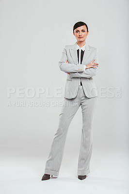 Buy stock photo Studio portrait of an attractive and confident businesswoman posing against a gray background