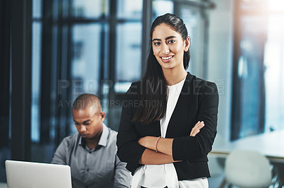 Buy stock photo Portrait of a young businesswoman standing in an office with her colleague in the background
