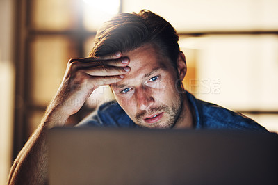 Buy stock photo Cropped shot of a handsome young male designer looking stressed while working late in his office