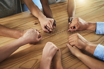 Buy stock photo Cropped shot of a group of businesspeople sitting together at a table and holding hands