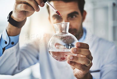 Buy stock photo Shot of a scientist conducting an experiment in a lab