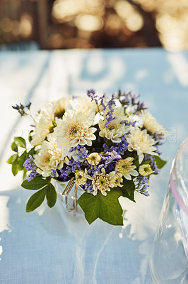 Buy stock photo High angle shot of a vase filled with flowers on a table at a tea party outside