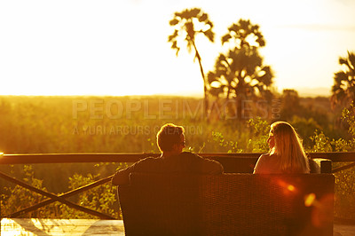 Buy stock photo Cropped shot of a young married couple having a drink outside at a resort in nature