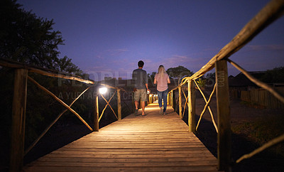 Buy stock photo Rearview shot of an unrecognizable couple walking on a bridge at a resort in nature