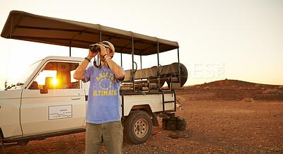 Buy stock photo Shot of a young man using binoculars while on a safari