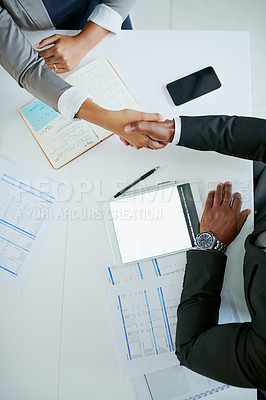 Buy stock photo High angle shot of two businesspeople shaking hands during meeting in an office
