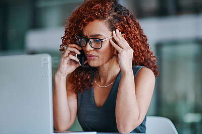 Buy stock photo Shot of a young businesswoman looking stressed out while talking on a cellphone in an office