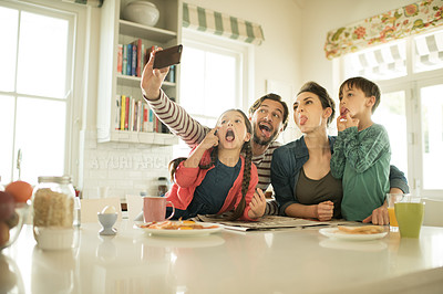 Buy stock photo Shot of a family making silly faces while taking selfies together at home