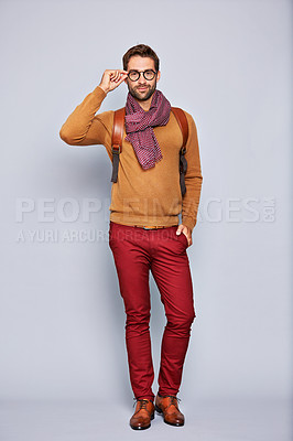 Buy stock photo Studio portrait of a handsome young man adjusting his glasses against a grey background