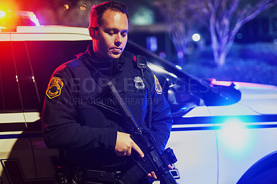 Buy stock photo Cropped shot of a handsome young policeman standing with his assault rifle while out on patrol