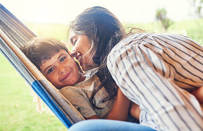 Buy stock photo Cropped shot of an attractive young woman and her son bonding outside on the hammock