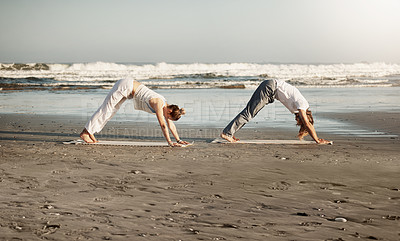 Buy stock photo Shot of a young couple practising yoga together on the beach