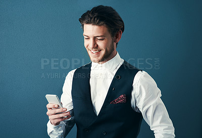 Buy stock photo Studio shot of a handsome young businessman sending a text message against a blue background