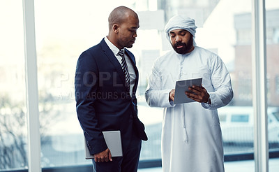 Buy stock photo Shot of two businessmen using a digital tablet while having a discussion in a modern office