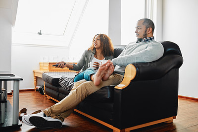 Buy stock photo Shot of a young couple watching tv while chilling on the couch in the living room at home
