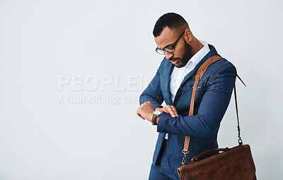 Buy stock photo Studio shot of a well dressed young businessman checking the time on his watch