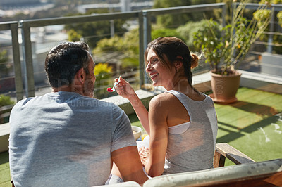 Buy stock photo Rearview shot of a mature couple enjoying breakfast together outdoors