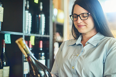 Buy stock photo Shot of a young sommelier in a wine cellar