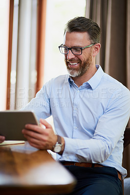 Buy stock photo Shot of a mature businessman using a digital tablet to work from home