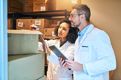 Buy stock photo Shot of a young woman and mature woman using a digital tablet while doing inventory in a pharmacy storeroom