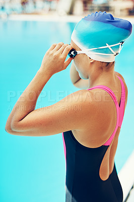 Buy stock photo Cropped shot of a young female swimmer adjusting her goggles before a swim