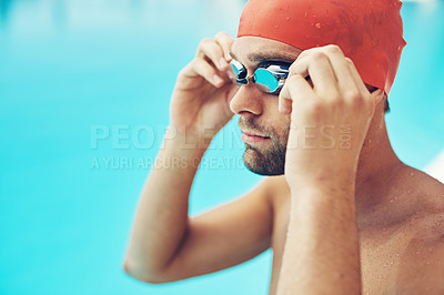 Buy stock photo Cropped shot of a handsome young male swimmer adjusting his goggles before a swim