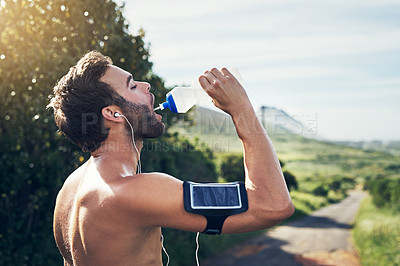 Buy stock photo Cropped shot of a handsome young male athlete drinking water while out for his morning run