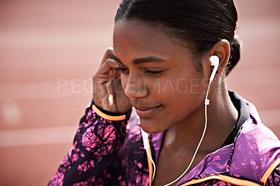 Buy stock photo Cropped shot of a young athlete listening to music while out on the track