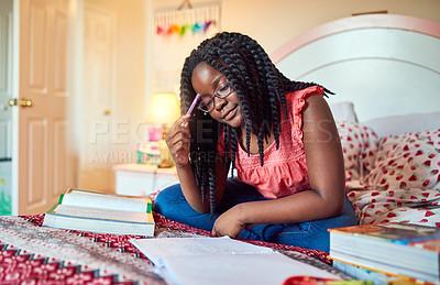 Buy stock photo Shot of an adorable little girl doing her homework on her bed in her bedroom