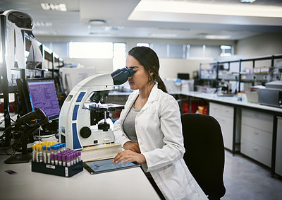 Buy stock photo Shot of a young woman using a digital tablet and microscope while working in a laboratory