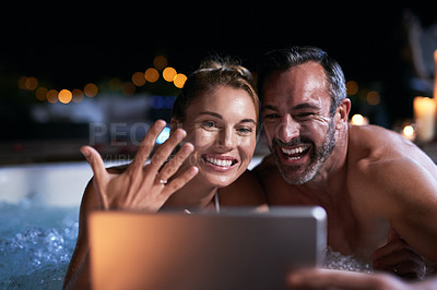 Buy stock photo Cropped shot of an affectionate mature couple announcing their engagement over video chat while relaxing in a hot tub