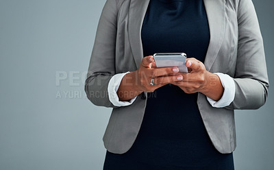Buy stock photo Closeup shot of an unrecognizable businesswoman using a cellphone against a grey background