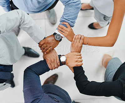 Buy stock photo High angle shot of a group of unrecognizable businesspeople holding onto one another while standing in a huddle in the office lobby