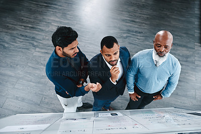 Buy stock photo High angle shot of three businessmen brainstorming together on a whiteboard in an office