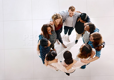 Buy stock photo High angle shot of a group of young businesspeople huddled together in solidarity in a modern office