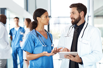 Buy stock photo Cropped shot of a male doctor and a female nurse using a tablet in the hospital with their colleagues in the background