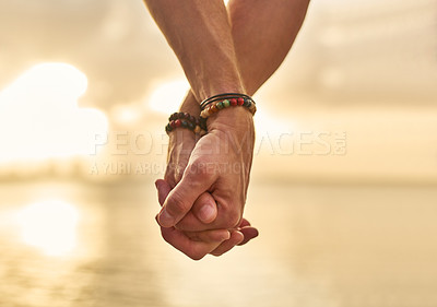 Buy stock photo Closeup shot of an unrecognizable couple holding hands while spending the day by the beach
