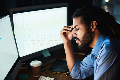 Buy stock photo Shot of a young designer looking stressed out while working late in an office
