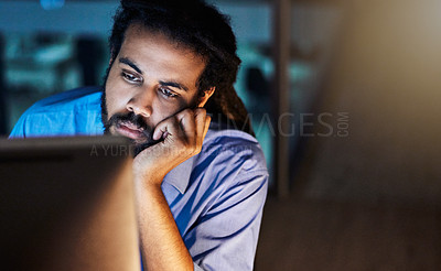 Buy stock photo Shot of a young designer looking bored while working late in an office