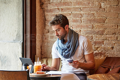 Buy stock photo Shot of a customer using his cellphone and digital tablet in a cafe